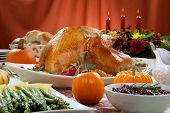 image of kumquat  - Roasted turkey on a server tray garnished with fresh figs grape kumquat and herbs on fall harvest table - JPG