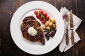 foto of ribeye steak  - Grilled steak Ribeye with herb butter and baby potatoes on white plate on wooden background - JPG