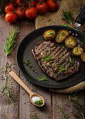 stock photo of ribs  - Beef rib eye steak with rustic potatoes fresh herbs and tomatoes sprinkled sea salt and herbs - JPG