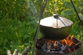 picture of cauldron  - Cooking in the cauldron on fire place - JPG