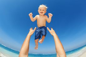 picture of children beach  - Father hands tossing up the high air joyful baby boy in on white sand sea beach - JPG