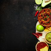 Mexican food concept: tortilla chips, guacamole, salsa, chilli with beans and fresh ingredients over poster