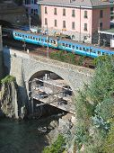 Blue Local Train Passing A Bridge Over The Sea In Riomaggiore Village, The Cinque Terre, Italia
