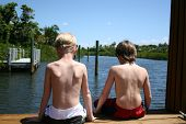 Boys Sitting On Dock Enjoying The Scenic View Of The Bay