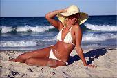 Menina loira sexy do bronzeado na praia