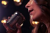 Extreme close-up of female hand holding a vintage microphone. Woman sings in microphone. Microphone  poster