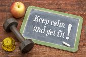 Keep calm and get fit -  slate blackboard sign against weathered red painted barn wood with a dumbbe poster