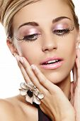 stock photo of blonde woman  - beautiful blond woman with long false eyelashes and pink eyeshadow and lipstick wearing large cocktail flower ring with a surprised expression - JPG