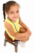 Adorable 3 year old hispanic african american girl sitting on stool over white background.