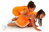 Two adorable african-hispanic girls playing basketball in uniform. Clipping path over white.