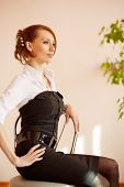 Slim beautiful woman strictly dressed sitting on the chare at interior.