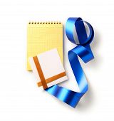 Blank greeting card with blank yellow spiral note book and curved ribbon. Isolated.