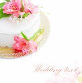Half of wedding cake with fresh flowers on white background.