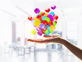 Close Of Businessman Hand Holding Cube Figure As Symbol Of Innovation. 3d Rendering poster