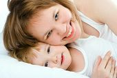 stock photo of happy kids  - mother and baby in bed - JPG
