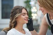 Smiling Makeup Artist Doing Professional Makeup To Charming Young Girl And Applying Lip Gloss In Bea poster