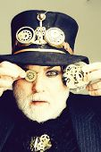Senior Bearded Man Or Watchmaker With White Beard In Black Hat Keeps Cogwheel And Mechanical Metalli poster