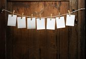 seven photo paper attach to rope with clothes pins on wooden background