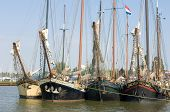A row of old sailing vessels, neatly arranged in the harbor