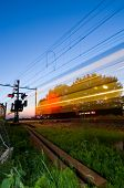 Un tren pasando un cruce de ferrocarril en la noche