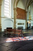 The interior of the Bavo Protestant Church in Haarlem, the Netherlands, with light cast through a stained window on the church floor