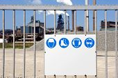 A galvanised steel gate with a safety regulation sign with plenty of copy space for your own message