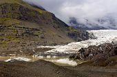 Ende der Svinafellsjokul, Island, mit einem schlammigen Pool mit Eisberge und Moränen, beleuchtet von einem glim