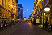 An alley with restaurants, displaying their specialties on a winter evening in Haarlem, the Netherla