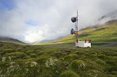 A communications tower in the Tundra of Iceland with a rainbow in the background