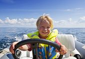 Young boy behind the steering wheel of an inflatable speedboat