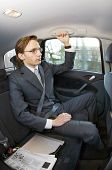 A businessman riding in the backseat of a taxi with laptop and newspaper next to him
