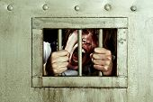 Cross-processed image of a man going insane, grabbing the bars of his jail cell, looking rabid and s