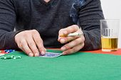 A player during a back room poker game toying with his cards, a cigarette in the other hand and a gl
