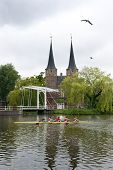 A rowing team in a coxed four rowing past a historic, fortified, city gate in Delft, the Netherlands