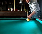 Pool player during a massee shot in a dimly lit bar