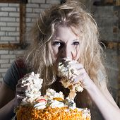 Young woman, ravaging a cake with both hands, eating uncontrollably