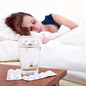 Glass of water and two strips of pills on a bedside table, with a sick woman sleeping in the backgro