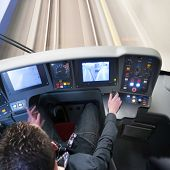 Train driver behind the dashboard controls of his carriage in the confined space of the cockpit