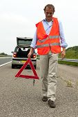 Man walking backwards from his car wearing a safety vest, carrying a warning triangle