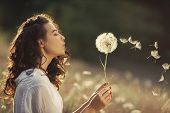 Beautiful Young Woman Sitting On The Field In Green Grass And Blowing Dandelion. Outdoors. Enjoy Nat poster