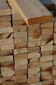 pic of 2x4  - 2x4 lying on a stack of wood to be used on a home - JPG