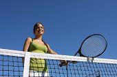 Feliz mujer morena con su raqueta de tenis
