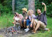Man Taking Photo Near Bonfire Nature Background. Tourists Sit Log Near Bonfire Taking Selfie Photo S poster