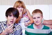 Amazed teens eat popcorn while watching movie
