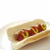 Hot dog on a bun on a white plate with ketchup and mustard