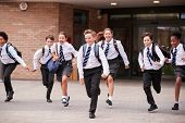 Group Of High School Students Wearing Uniform Running Out Of School Buildings Towards Camera At The  poster