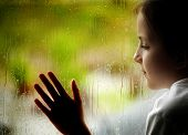 Little girl looking out window on a rainy day