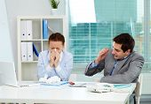 Image of businesswoman sneezing while her partner looking at her unsurely in office