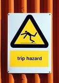 Trip Hazard sign on an orange tin wall