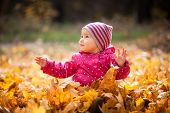 Little Kid Is Playing And Sitting In Fallen Leaves In Autumn Park. Baby Smiles. Girl Is Dressed In W poster